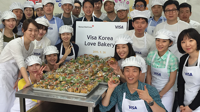 Sign of Korean Red Cross, Visa, Visa Korea Love Bakery, May 26, 2015, with bakers and goods gathered around signs.