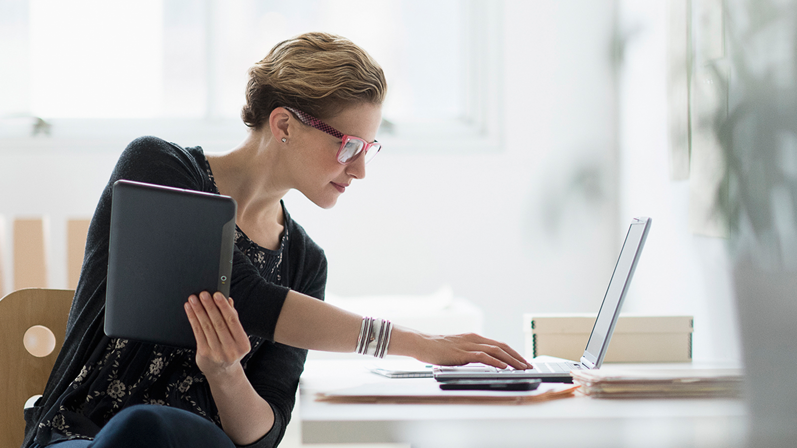 Woman seated at desk using laptop and holding a tablet with a smart phone nearby.