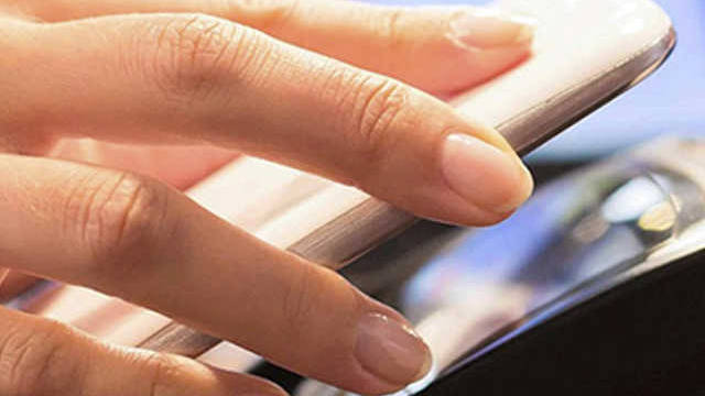 Close up of a hand holding a mobile phone next to a payment terminal.